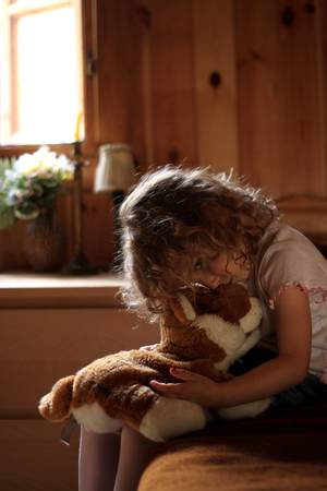 constraint: Depressed little girl hugging teddy bear