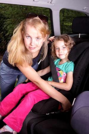 asiento coche: Mujer llevar el cinturón de seguridad en el asiento del bebé en el coche Foto de archivo