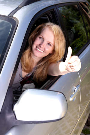Smiling girl  in car with thumb up photo