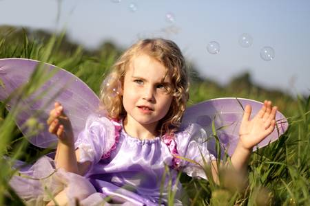 Girl fairy in the meadow catching soap bubbles photo