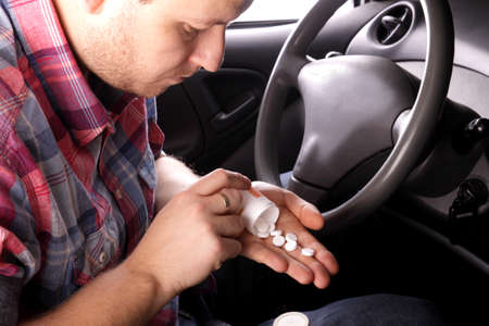 drunk party: Man swallows drugs in the car Stock Photo