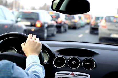 De chauffeur wacht in een grote verkeersopstopping in de auto