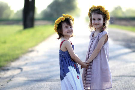 Two girls with garlands on his head holding hands photo