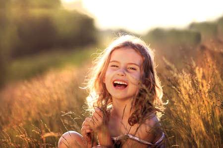 glädje: Bedårande liten flicka skrattar i en äng - glad tjej
