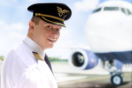 pilot cockpit: Smiling pilot goes into the plane Stock Photo