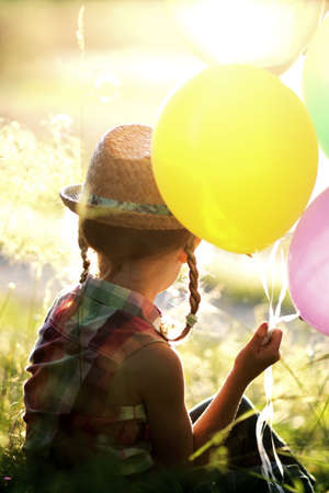 little girl in a hat with balloons sitting in a meadow photo