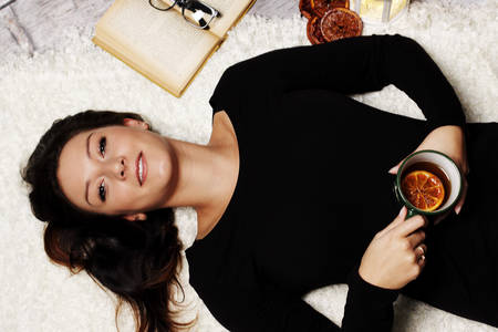 winter evening: Woman relaxes with a cup of tea on a winter evening