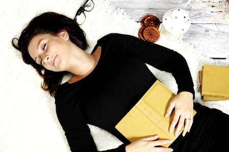 cheerful girl sleeping with a book photo