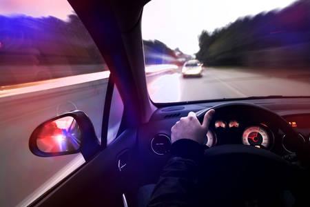 Der Verbrecher auf der Flucht vor der Polizei in einem gestohlenen Auto Standard-Bild - 24732968