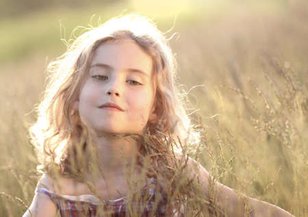 Young blonde girl on the summer meadow photo