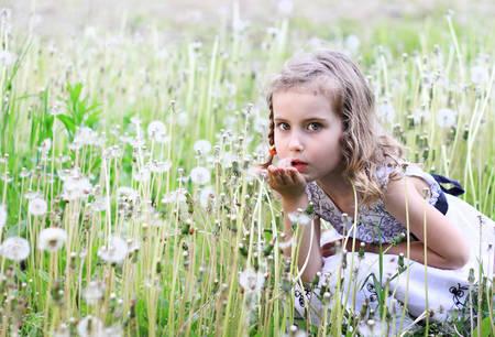 Girl blowing dandelion on a meadow photo