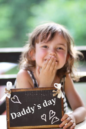 Joyful little girl holding a sign - daddy s day photo