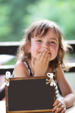 Joyful little girl holding a sign for your sample text photo