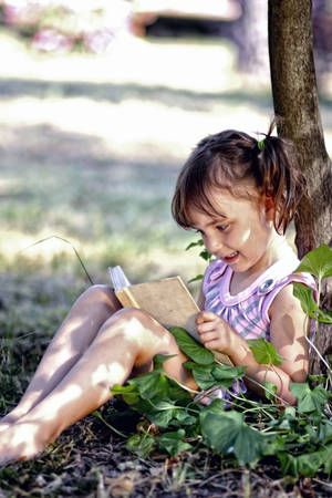 Adorable little girl in pigtails reading a book in the garden photo