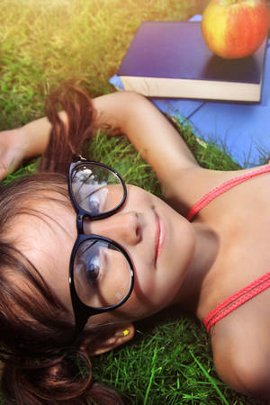 cuteness: Back to school - happy girl with glasses on the grass