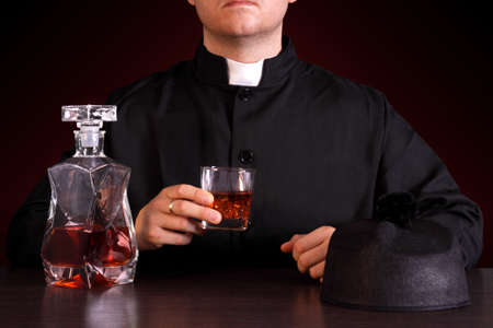 drinking alcohol:  priest drinking alcohol Stock Photo