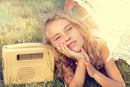 vintage radio:  Young girl listening to the radio on a sunny day