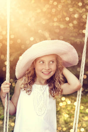 adorable little girl swinging on a swing photo