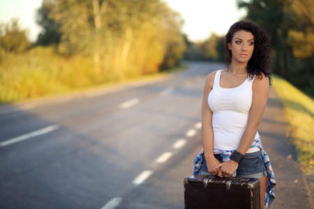 Beauty girl with old suitcase on the road photo