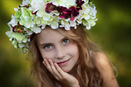 Beautiful smiling young girl in a wreath of flowers photo