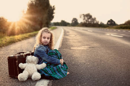 emigrant:  Lonely child with a suitcase and a teddy bear on road Stock Photo