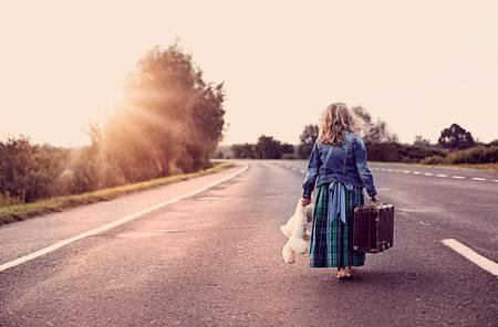 psicologia: Escapar de la casa - una niña con una maleta y un juguete