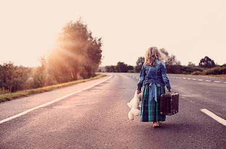Escape from the house - a little girl with a suitcase and a toy photo