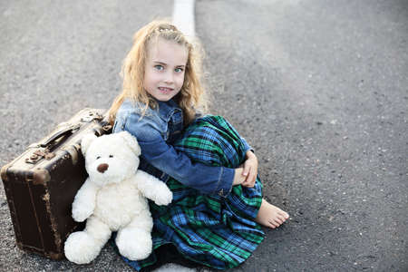emigrant:  Traveling alone young girl sitting on the street Stock Photo