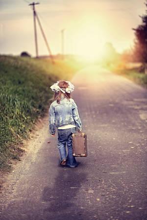 psicologia infantil: Una niña con una maleta vieja se embarca en un viaje Foto de archivo