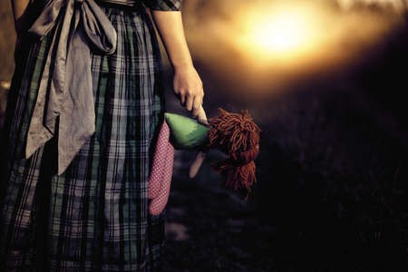 homeless children:  Loneliness - the girl with the doll goes to the light Stock Photo
