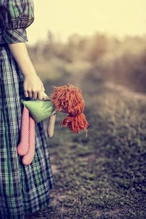 Muchacha sola triste en un vestido con una muñeca de trapo