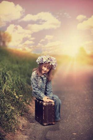 psicologia infantil: Niña alegre que se sienta en una maleta - gran viaje