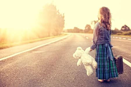 psicologia infantil: La chica en un vestido con una maleta que mira el sol Foto de archivo