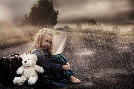 clochard: Ragazza solitaria da solo per la strada in una giornata piovosa