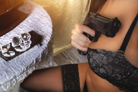 girl in lingerie with a gun in the dresser