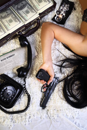 Girl in lingerie with a gun lying on the bed after the mugging photo