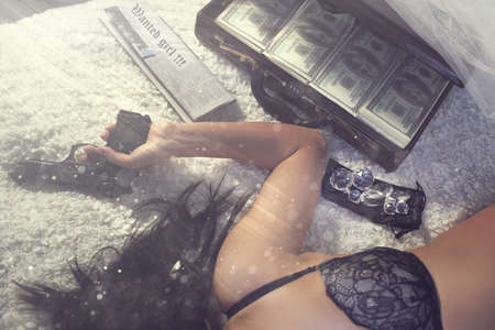 Girl in bra with loot lies in a dusty hotel room photo