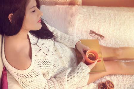 mujer pensativa: Chica joven en un blanco beber té suéter con limón Foto de archivo