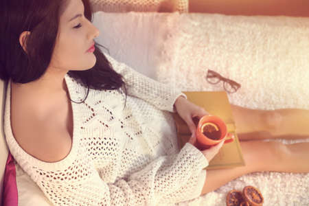 Young girl in a white sweater drinking tea with lemon Imagens