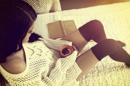 Girl in stockings rests with hot tea photo