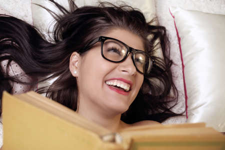 favorite book: girl laughs while reading a favorite book Stock Photo