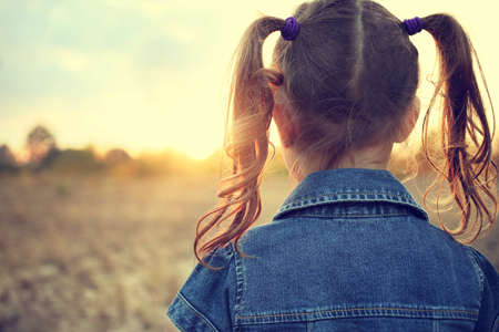 girl in braids looking at the sun in the evening on the meadow photo