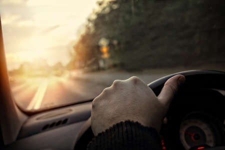 driving school: hand on the steering wheel - the driver drives into the sunset