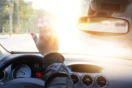 bestuurder verblind door de zon in de auto