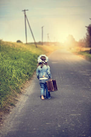 girl with a suitcase goes on an adventure photo