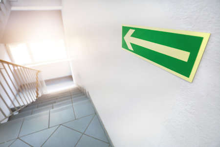 Emergency exit with green arrow sign photo