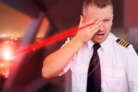Landing aircraft and the pilot blinded by laser from the ground photo