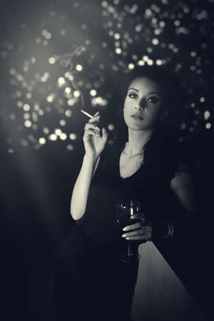 Hauntingly beautiful woman standing with a cigarette in evening gown at the bar photo