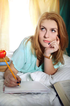 beautiful thoughtful girl learns to test at home photo