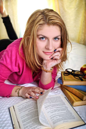 Pensive and smiling student girl reading a book photo